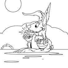 Desenho para colorir de um coelhinho da Páscoa com um ovo
